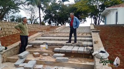 Bizzarri visitando a obra e orientando a construção da escada de pedra com pedra folheta com a mureta de pedra com paralelepípedo rachado nesse tom de cor de pedra cinza escuro em sede da Fazenda em Atibaia-SP.