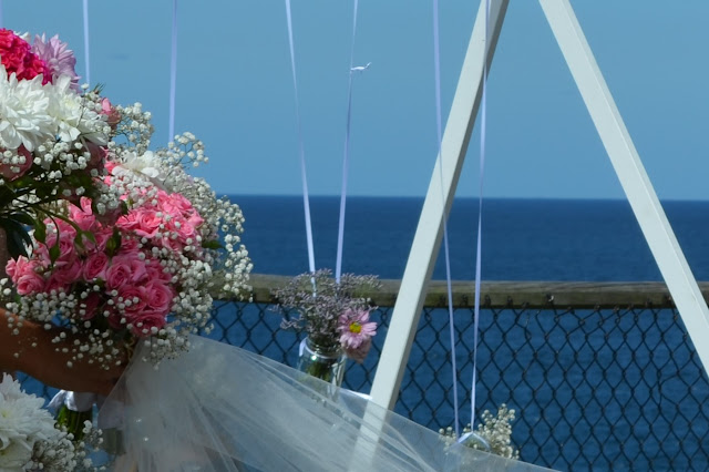 A wedding scene in blue, white and pink.  The deep blue ocean and clear blue sky is the backdrop to wedding decorations of jam jar posies suspended on white ribbons, hanging from a white trestle frame. A bridal bouquet in pink and white is on the left hand side with a horizontal spread of white tulle across the bottom. A wooden-framed wire mesh fence sits between the trestle and the ocean view.