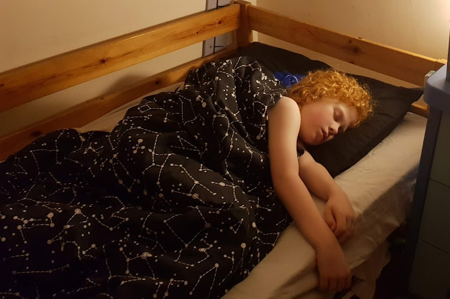 Child sleeping in bed showing Dreamtex NASA bedding with constellation design