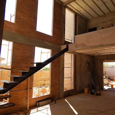 A escada que liga a sala de estar ao mezanino da casa com pé-direito duplo foi concebida com estrutura metálica para receber placas de madeira, proporcionando um perfil aparente e integrado com as grandes janelas para um jardim lateral.