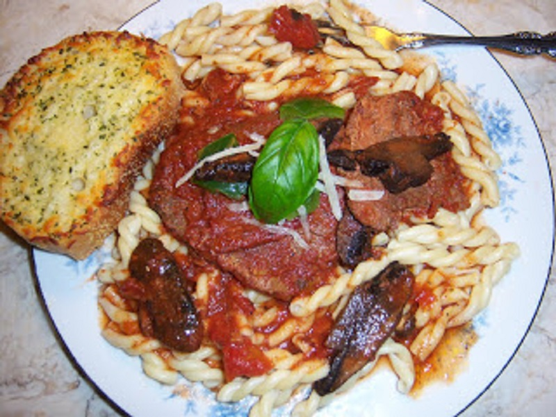 Italian sauce steak is inexpensive cuts of meat like cube or in the photo round steak with crushed tomatoes simmered in a pan with button mushrooms and peppers until fork tender served or pasta or rice