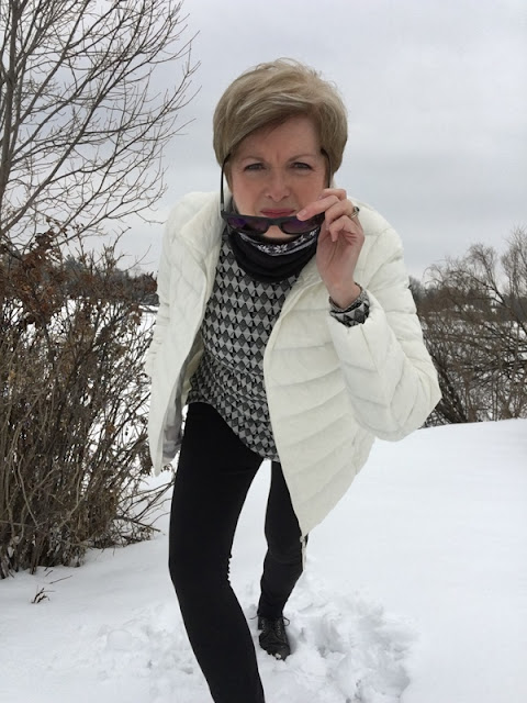 woman in black pants, white jacket and black and white top and neck warmer, peering into the camera lens