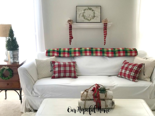 farmhouse Christmas living room white couch birch logs rosemary tree striped stockings
