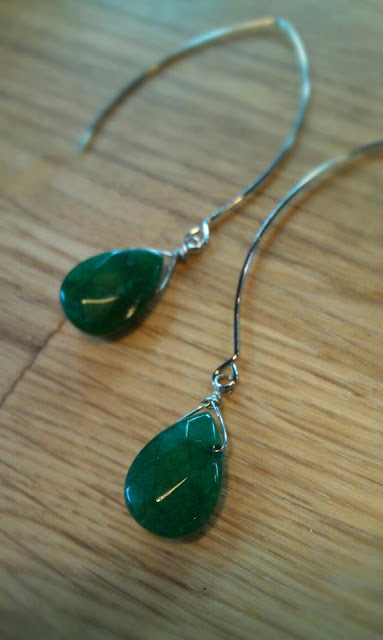 pair of v earrings with a jade stone