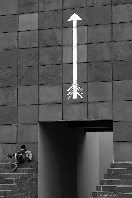 A Black and White Minimal Art Photograph of a Person Sitting cross legged on the stairs at Jawahar Kala Kendra, with a Big White Arrow on the wall next  to him