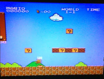 [Image: A somewhat blurry photo of an LCD TV showing Super Mario Bros.]