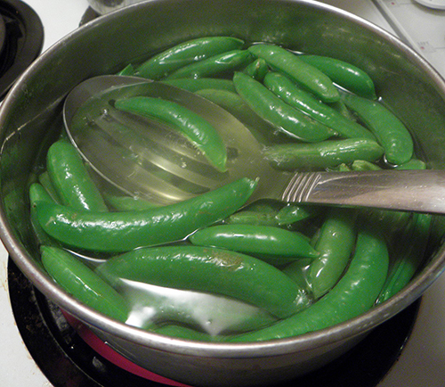 Peas done and being scooped out of boiling water