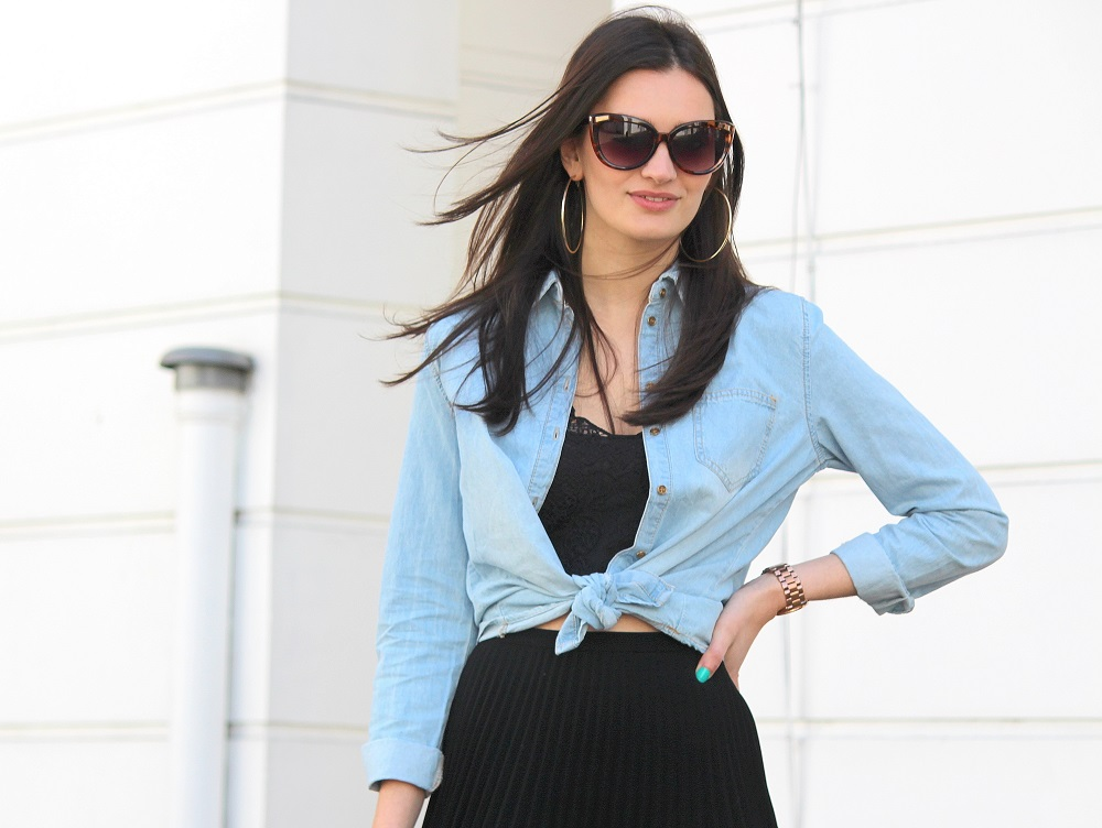 peexo fashion blogger wearing pleated midi skirt with lace bralet and denim shirt and sunglasses in spring