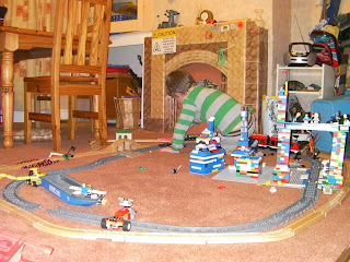 lego train set and wooden train track arrangement