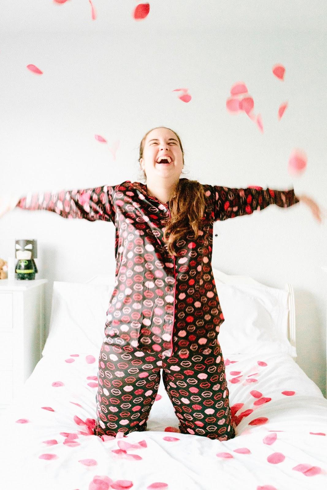 Girl wearing kiss print satin Victoria's Secret Valentine's Day pajamas