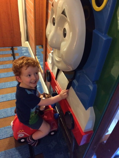 Little boy sitting on a trunki next to Thomas wall feature