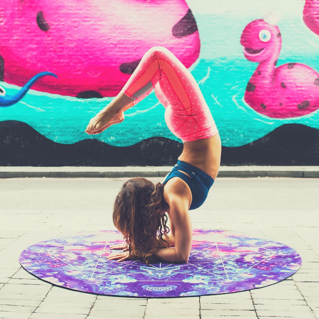Woman does yoga on a purple mat.