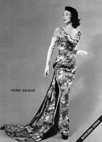 Model Dorian Leigh posing in floral evening dress by Pierre Balmain