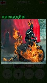 каскадер на горящем мотоцикле едет и выполняет трюк