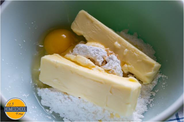 cream together butter, powdered sugar, egg, vanilla and almond extract