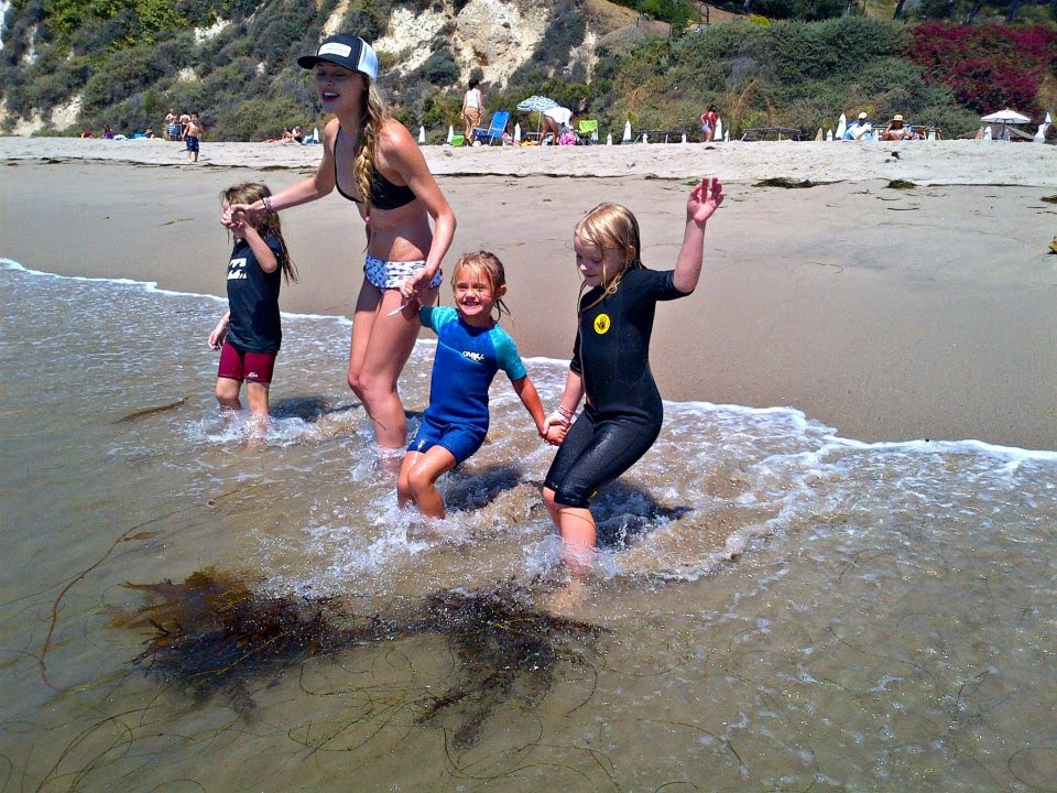 Three little girls and their camp counselor holding hands entering the ocean at Aloha Beach Camp in Malibu.