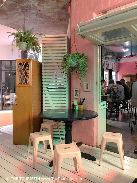 Low stools around a small black wooden table standing on a white painted wooden floor. The room is decorated with plants and lights and is painted in pink. In the background there is a group of people eating while sitting on high bar stools.