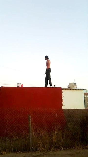 Joven con arma blanca sobre el techo de una vivienda
