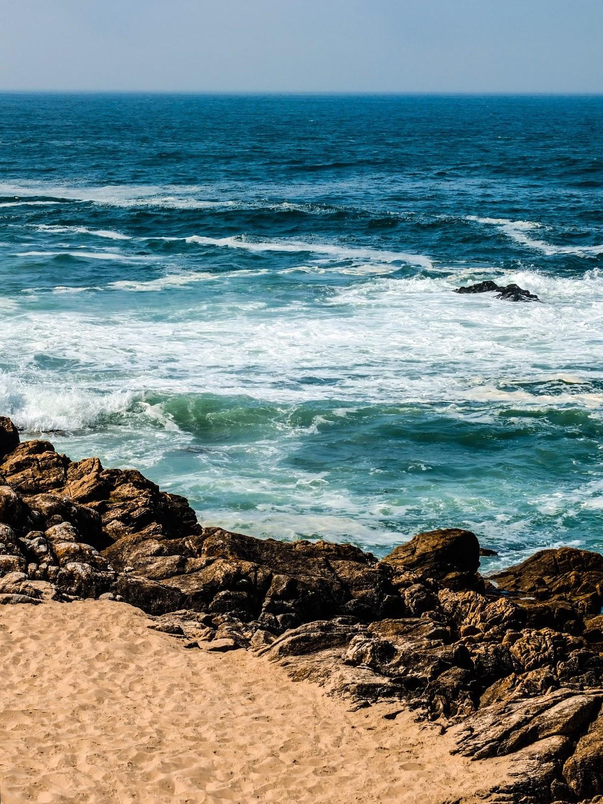 Waves crashing on rocks in Porto, Portugal.