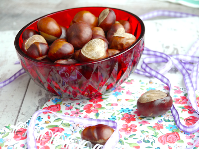 a red glass bowl holding lots of conkers, surrounded by lilac ribbon