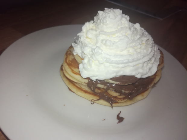 stack of pancakes with whipped cream and nutella