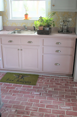 pink counter top and cabinets with painted brick floor