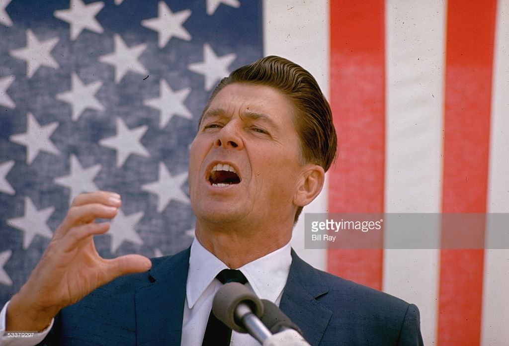 Ronald Reagan wows the crowd in front of the Stars and Stripes