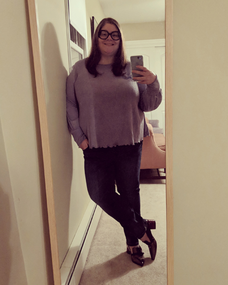 image of me standing in a full-length mirror, leaning to one side with one angle crossed over the other, with my hair down, wearing large black-framed glasses, a purple top, dark blue jeans, and burgundry and grey heeled shoes