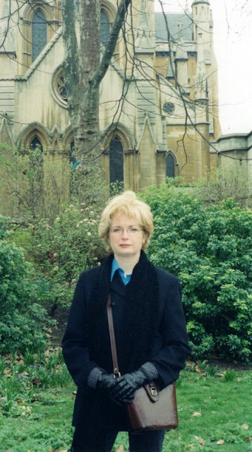 woman in front of a church spire wearing a black jacket and scarf