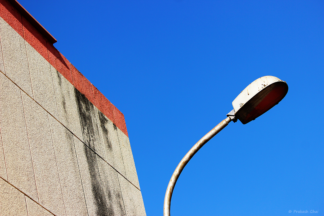 A minimalist photo of A downward trending red line leading to an upward curve of a street light.