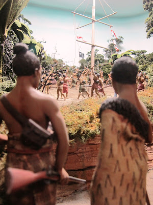 Diorama of 19th-century Maori with muskets on a track in the bush, watching a crowd of people around a flagpole in the distance.