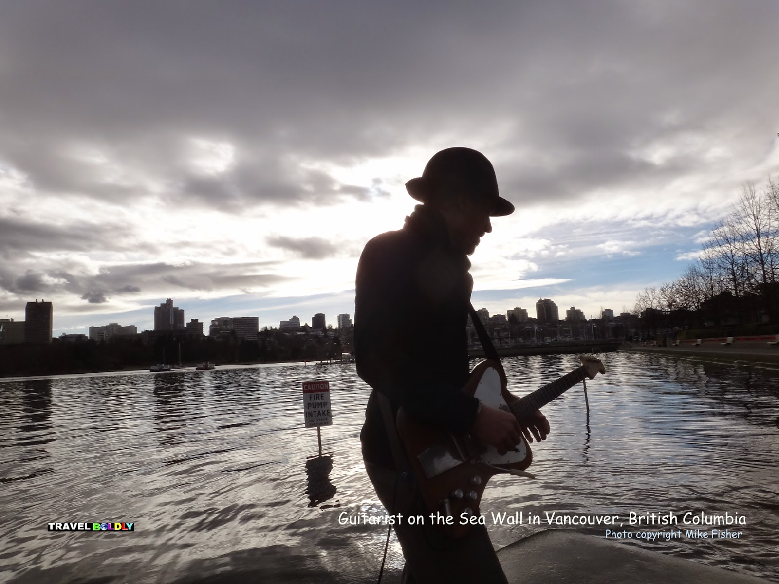 Guitarist Peter Jack Rainbird on the Vancouver waterfront - Vancouver, British Columbia - Photo Mike Fisher for Travel Boldly