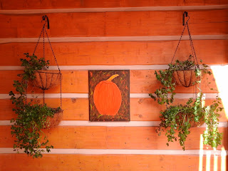 Covered entrance to condos with 2 baskets of herbs growing over the edge with a pumpkin fall sign hanging in the middle.