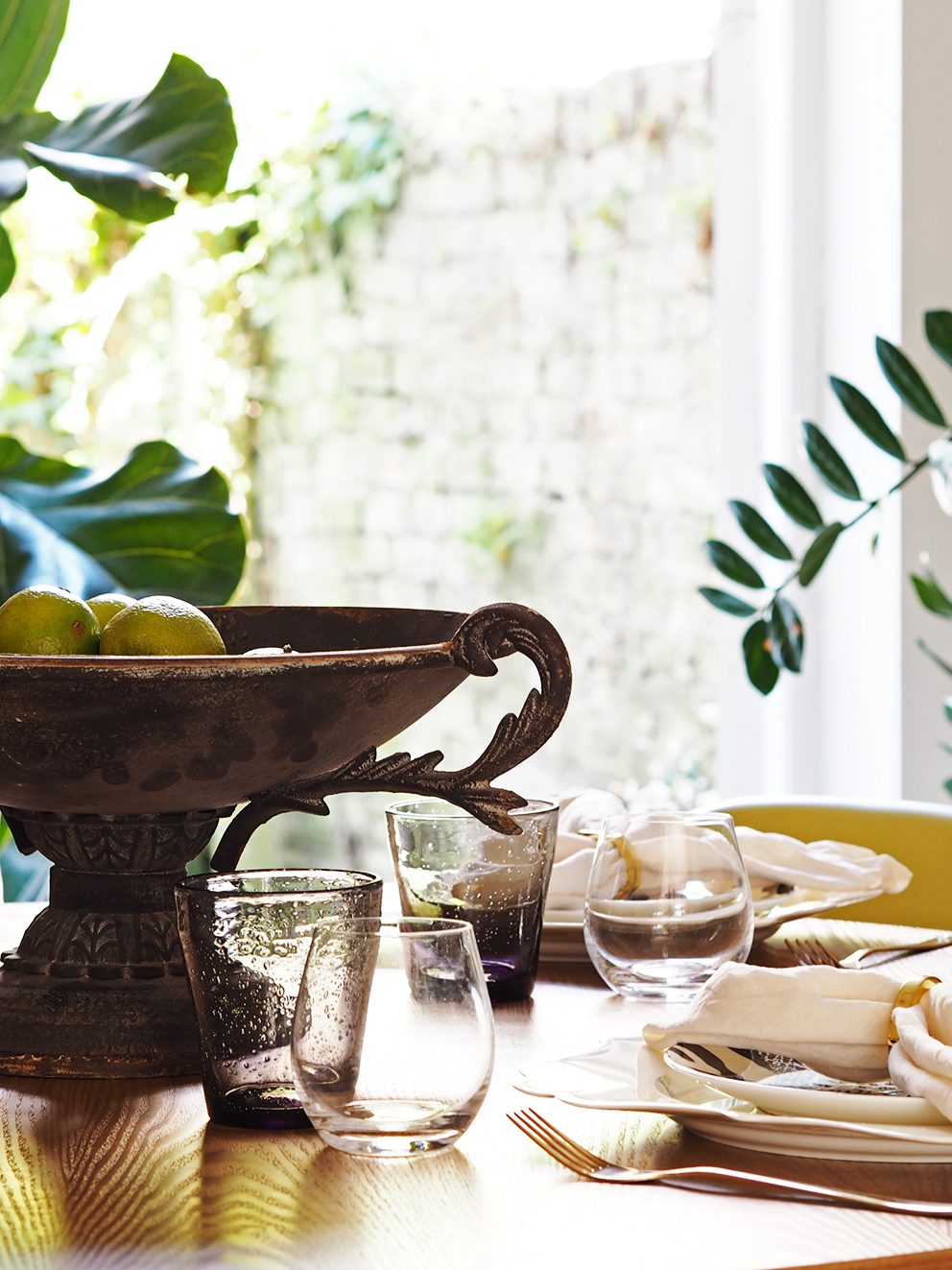 My Summer Dining Room - French For Pineapple Blog - table setting with ornate footed bowl of limes, stemless wine glasses and tinted tumblers