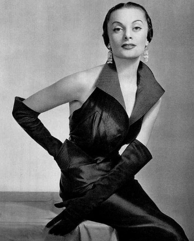 Maggy Sarrange in black satin halter dress with wide lapels  Designer Maggy Rouff 1950