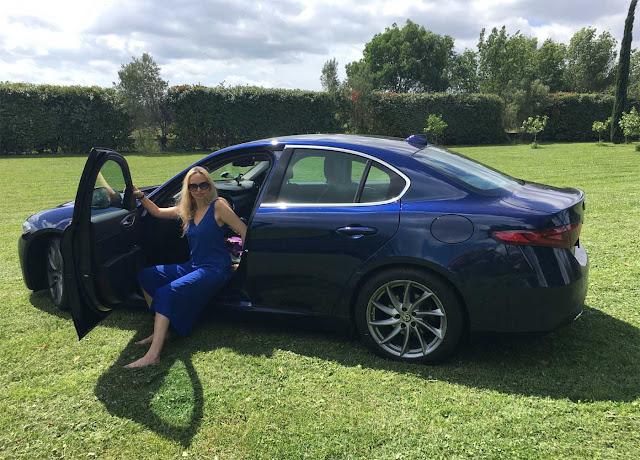 Model sitzt auf Vordersitz der Alfa Romeo Giulia Super , Shooting Location ist grüner Rasen