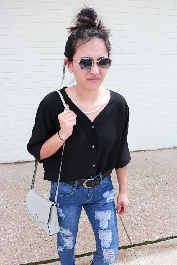 Black button-up blouse, jeans, simple silver necklace, circle sunglasses, gray bag