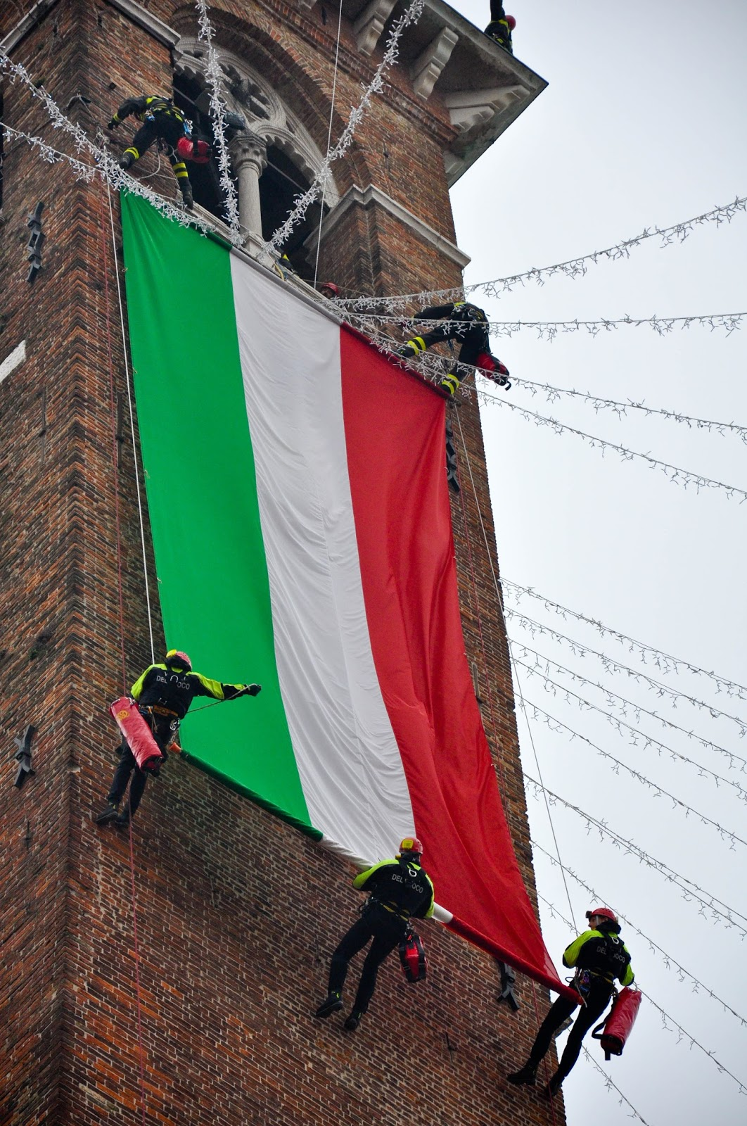 Firefighters unfurling the Italian flag down the clock tower of Palladio's Basilica, Saint Barbara celebration, Vicenza, Veneto, Italy