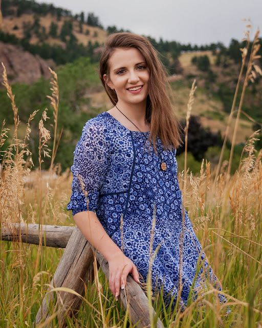 a woman poses in a meadow with tall grass for her senior portraits in Boulder Colorado