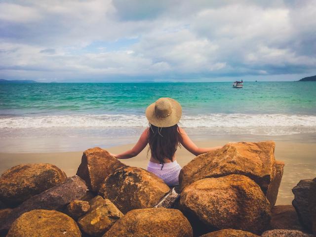 Ellen sentada nas pedras da praia