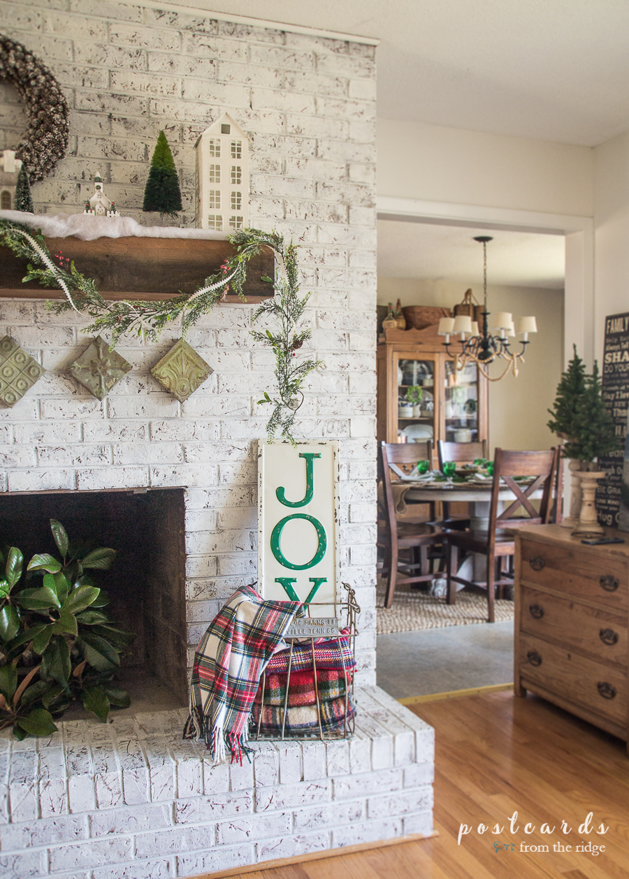 farmhouse style white painted brick Christmas mantel with metal JOY sign
