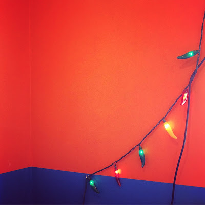 multicolor chile pepper lights against a wall painted orange on top and blue on bottom
