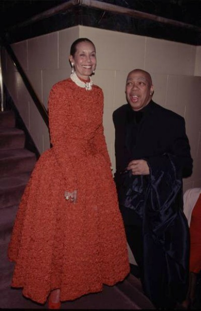 Carmen de Lavallade in red evening gown and Geoffrey Holder in black tie posing for cameras