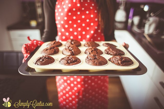 a woman wearing an apron holds fresh baked muffins.