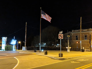 the US Flag on the downtown triangle at night