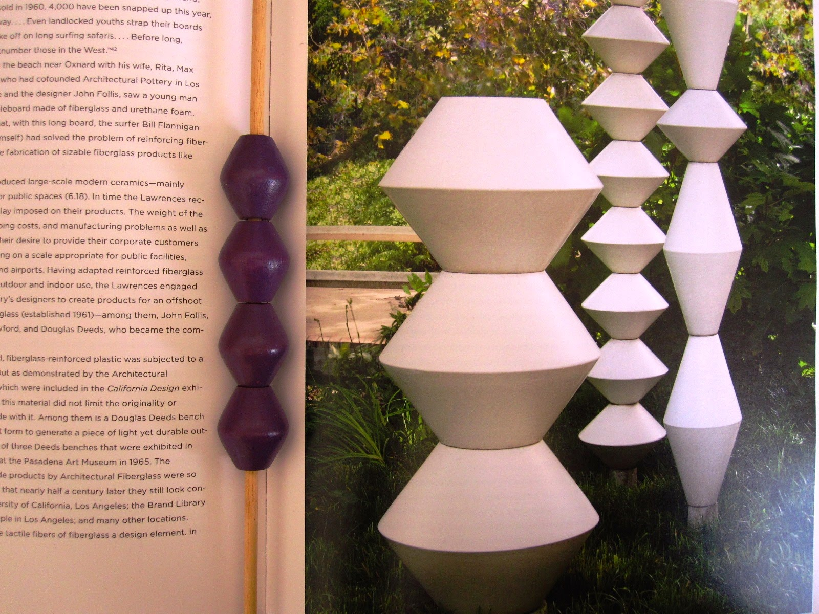 Picture in a book of La Gardo Tackett's garden sculptures, with four purple wooden beads lined up next to it.
