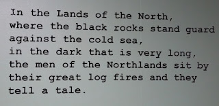 "Typed text: ""In the Lands of the North, where the black rocks stand guard against the cold sea, in the dark that is very long, the men of the Northlands sit by their great log fires and they tell a tale."""