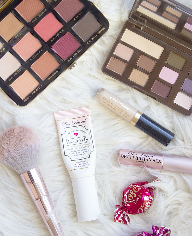 Brand feature of Make Up brand Too Faced. Flatlay of eyeshadow, mascara, concealer, lipsticks