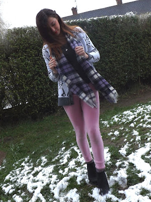 A person wearing a panda cardigan and lilac tartan scarf