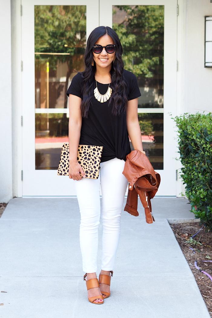 black twist tee + leopard print clutch + white jeans + cognac